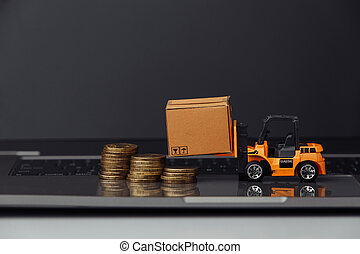 Mini forklift with carton boxes snd coins on keyboard. Logistics and delivery concept