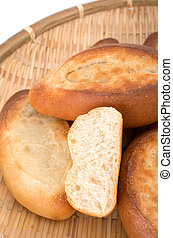 Mini french baguettes in a bamboo plate on white background