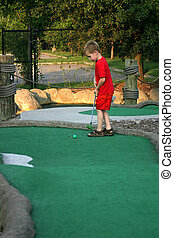 Mini-Golf Anyone? - A little boy playing mini-golf.