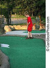 A little boy playing mini-golf.