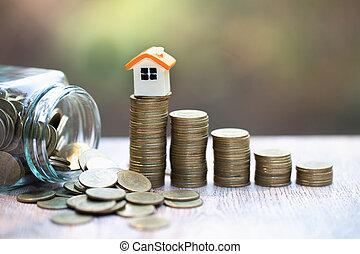 Mini house on stack of coins. Concept of Investment property and Risk Management.