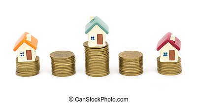 Mini house on stack of coins, Concept of Investment property, Investment risk and uncertainty in the real estate housing market. isolated on white background.