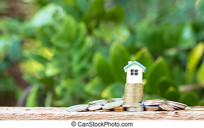 Mini house on stack of coins. Concept of Investment property.