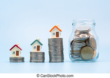 Mini house on stack of coins on a blue background. Concept of Investment property, Real estate, Saving money.
