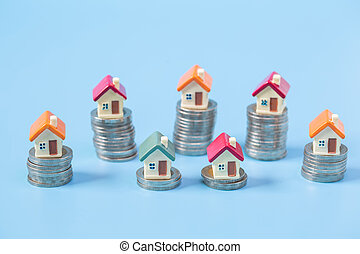 Mini house on stack of coins on blue  background. Concept of Investment property and Risk Management.