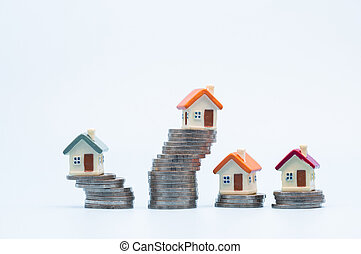 Mini house on stack of coins on white background. Concept of Investment property and Risk Management.
