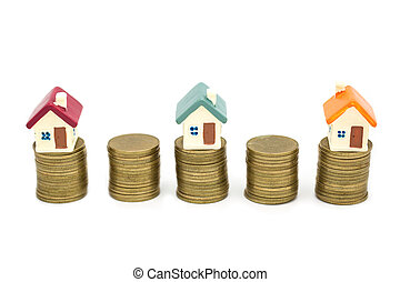 Mini house on stack of coins, Real estate investment concept and real estate business growth isolated on white background.