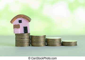 Mini house on stack of coins. saving money for buy home concept