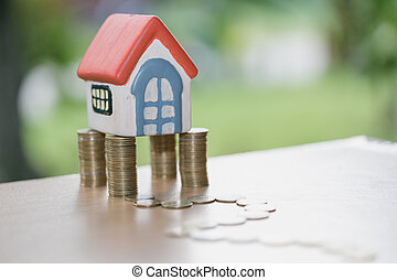 Mini house on stack of coins