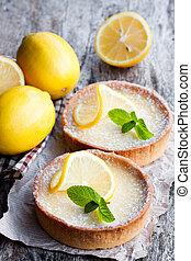 Mini lemon tarts on wooden table