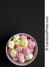 Mini meringues in a pink bowl over black background, top view. From above, overhead view. Close-up. Copy space.