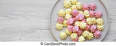 Mini meringues on a plate over white wooden background, top view. Flat lay, from above, overhead. Space for text.