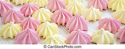Mini meringues on a white wooden background, side view. Close-up.