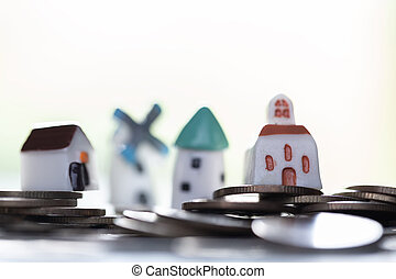 Mini model house on stack of coins. Concept of Investment property.