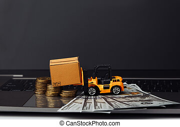 Mini model of forklift with boxes and money on keyboard. Logistics and delivery concept
