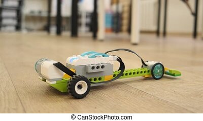 Mini model of plastic electronic car moves dow the floor...