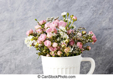Mini pink rose flowers in white cup