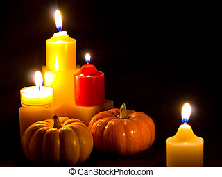 Mini Pumpkins and Candles with a Black Cloth Background