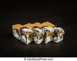 Mini-set of two types of rolls in the Japanese style on a dark background side view