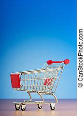 Mini shopping cart against gradient background
