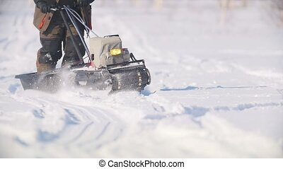 Mini snowmobile overcoming deep snow, specialized vehicle