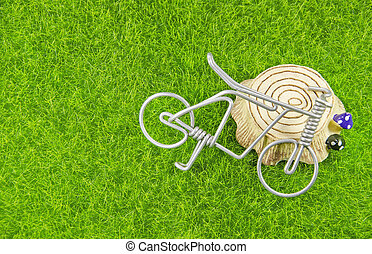 mini toy bicycle and tree stump on a grass