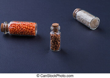 Mini transparent glass bottles with closed brown cork lids filled with uncooked grains.