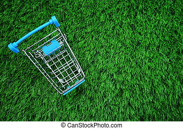 Mini trolley cart with space copy on green grass background