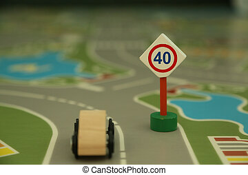 "mini wooden road sign ""speed limit 40"" and mini wooden car - imitation of a typical situation on the street. Abstract understanding of a message: ""Respect the rules of the game, negociation, society where you live and do not allow yourself to violate them"""