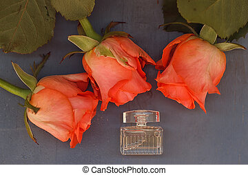 miniature bottle of perfume next to the three roses