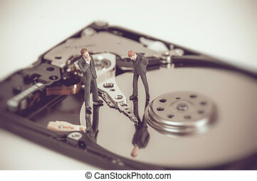 Miniature business people on top of hard drive. Business concept