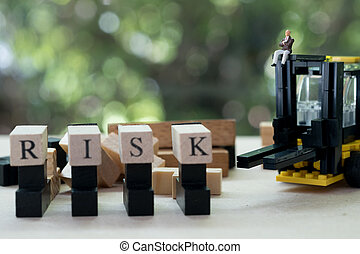 Miniature businessman sitting on forklift with wooden word RISK. Concept of risk assessment