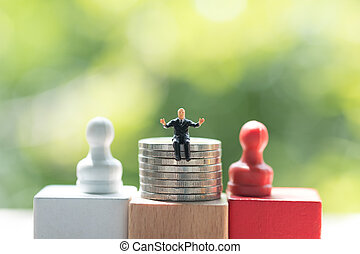 Miniature businessman sitting on stack of coins