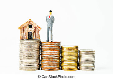Miniature businessman with little home model.