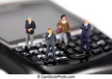 Miniature businessmen and businesswomen on a cellphone