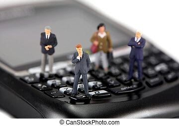 Miniature businessmen and businesswomen on a cellphone