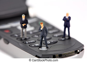 Miniature businessmen on a cellphone