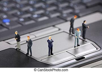 Miniature businessmen on a laptop