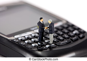 Miniature businessmen shaking hands on a cell phone -...