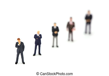 Miniature businessmen standing in a row diagonally