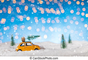 Miniature car carrying a Christmas tree in snow