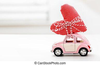 Miniature car carrying red heart cushion