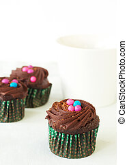 Miniature chocolate cupcakes and coffee