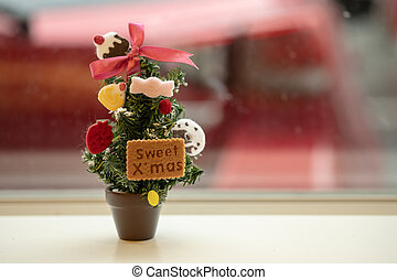 Miniature Christmas tree on the table near window