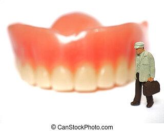 Miniature elderly standing on removable denture, on white background. Dental health concept.