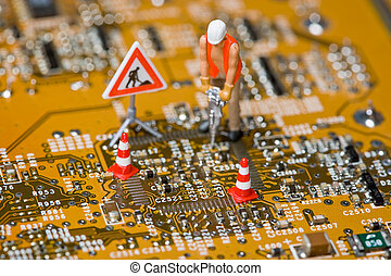 Miniature figures working on a circuit board.