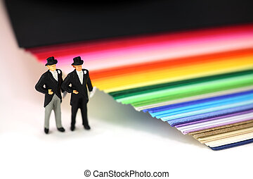 Miniature homosexual couple in tuxedos standing next to...