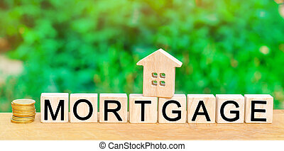 """Miniature house and dollars. Wooden blocks and the inscription """"mortgage"""". credit for property / apartment. Business loans for real estate concept. mortgage insurance"""