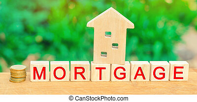 """Miniature house and money. Wooden blocks and the inscription """"mortgage"""". credit for property / apartment. Business loans for real estate concept. mortgage insurance"""