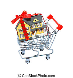 Miniature house in shopping cart isolated on white background